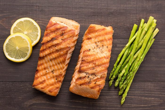 Grilled salmon with lemon, asparagus on the wooden background.