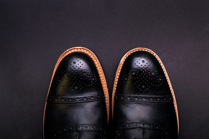 Black shoes with a brown sole on a black background