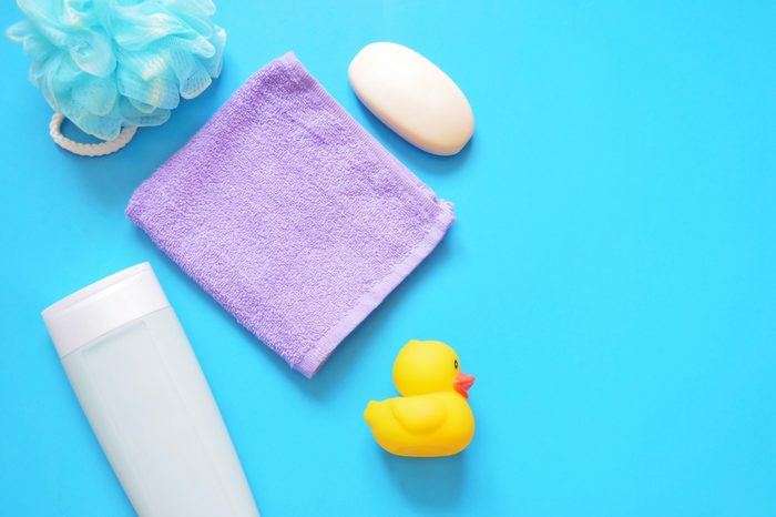 Sponge puff, shampoo bottle, purple towel, soap, yellow rubber duck on a blue background. Cosmetics for bathing babies. Flat lay bath products, top view photo. Free space for text, mock up