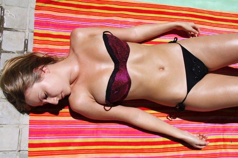 Woman sun tanning near swimming pool