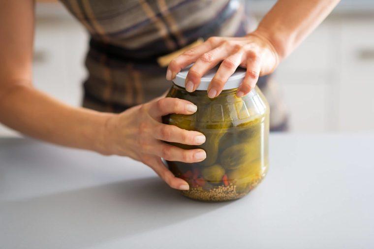 Housewife opening jar of pickles