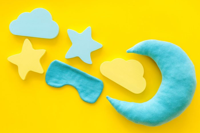 Night sleep concept with moon, clouds, stars toys and blindfold on yellow background top view