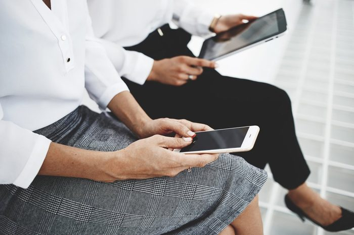 Closeup of woman is typing text message on mobile phone, while female near her is watching video on touch pad. Business women are booking on-line plane ticket via cell telephone and digital tablet