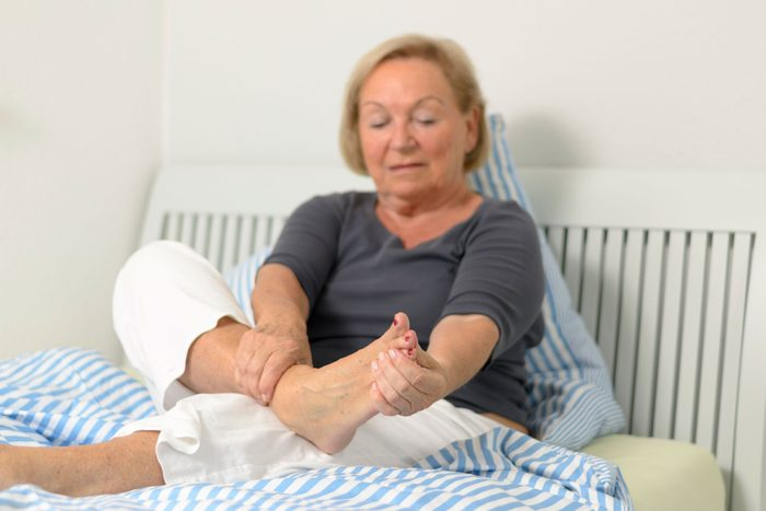 woman sitting in bed holding her foot