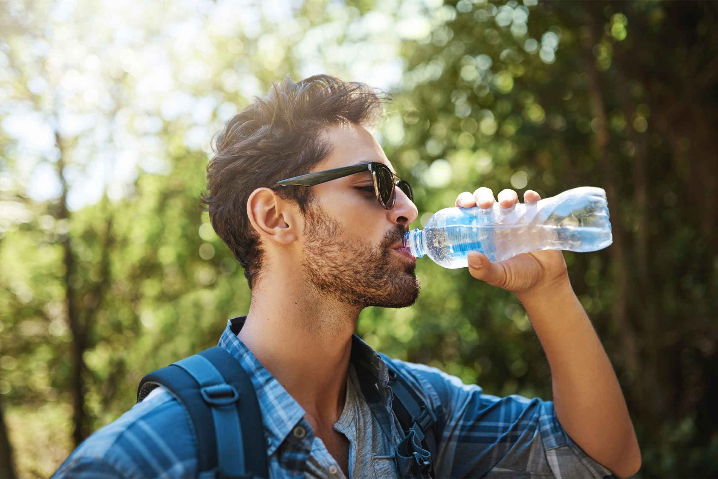 Handsome bearded man drinking from water bottle