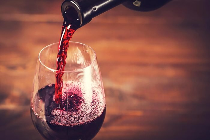 red wine pouring into a glass