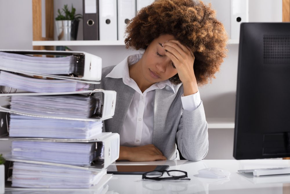 Stressful Afro American Businesswoman Sitting In Office With Stacked Of Files