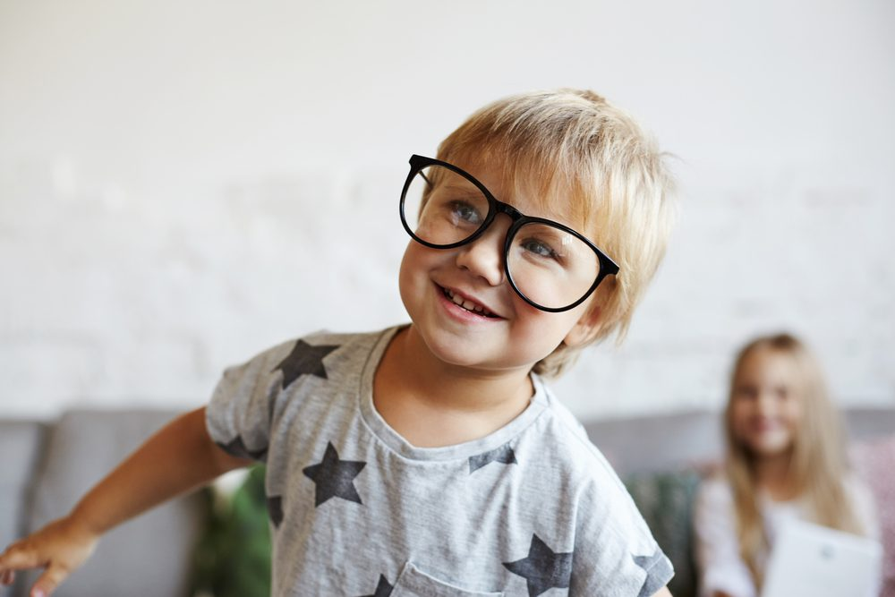 Funny 5-year old little Caucasian girl with short hairstyle wearing trendy eyeglasses and t-shirt with stars stretching arms widely as if imitating plane flight while playing at home with siblings