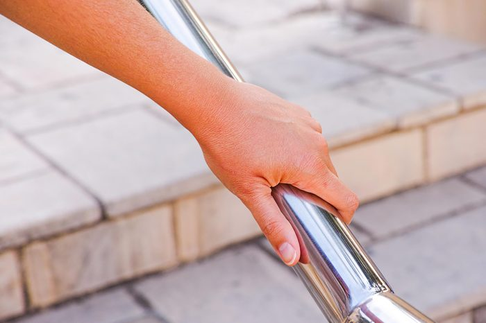 hand on an outdoor stair railing