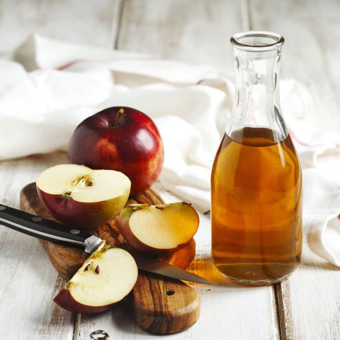Jug of apple cider vinegar and sliced red apples