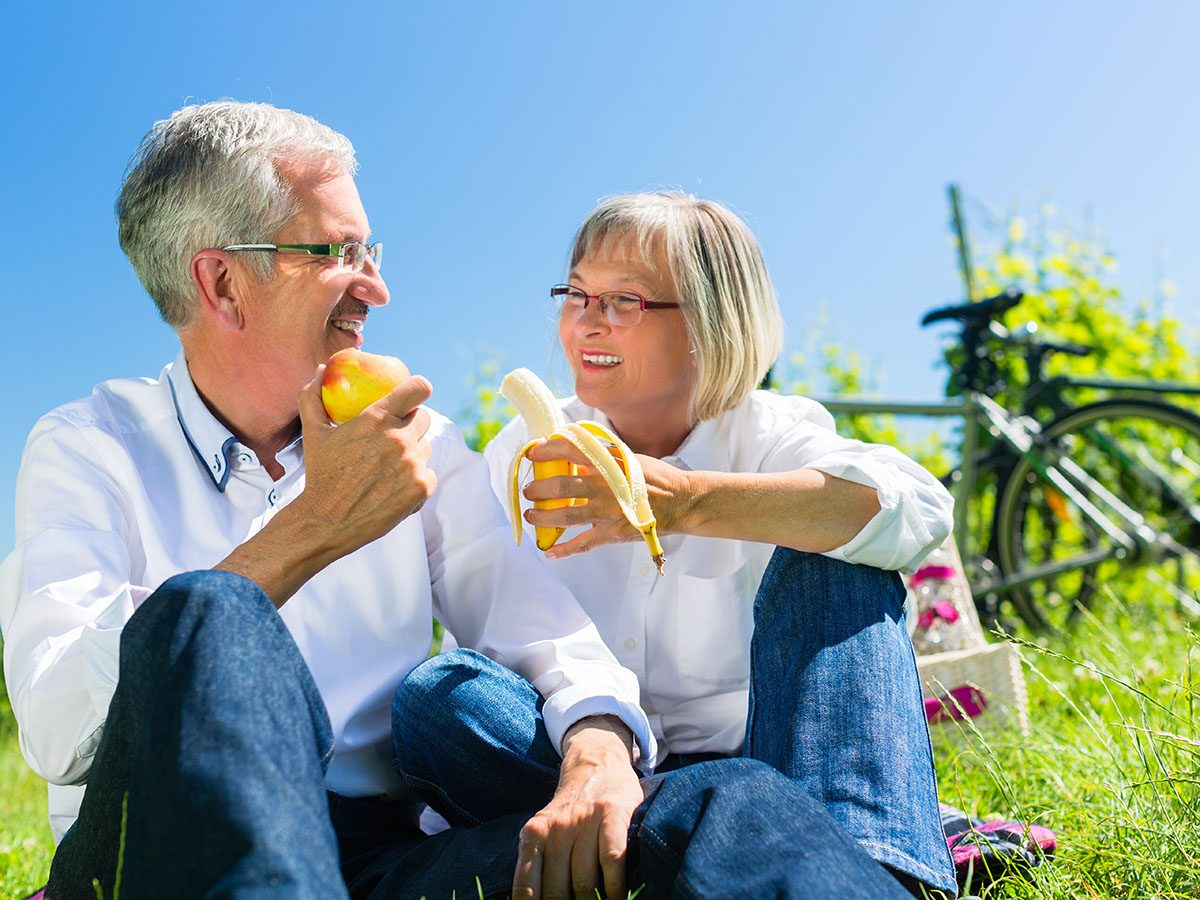 Older couple eating bananas.