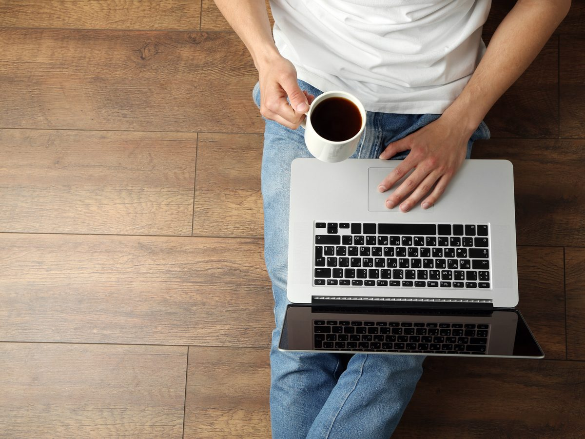 Man on laptop while drinking coffee