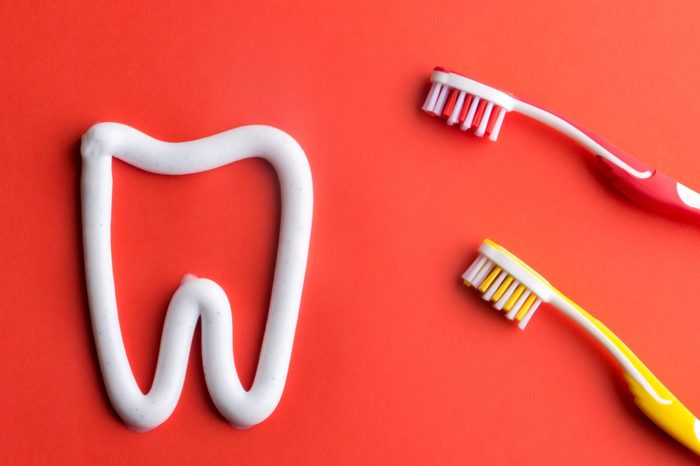 White toothpaste in a form of a tooth with red and yellow tooghbrushes on red background. White toothpaste and toothbrushes. Red and yellow tooghbrushes.