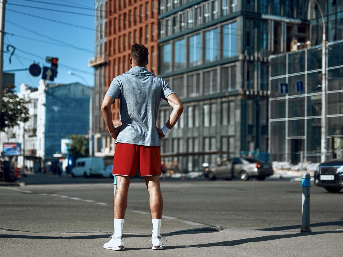 Young athletic man standing at a crosswalk