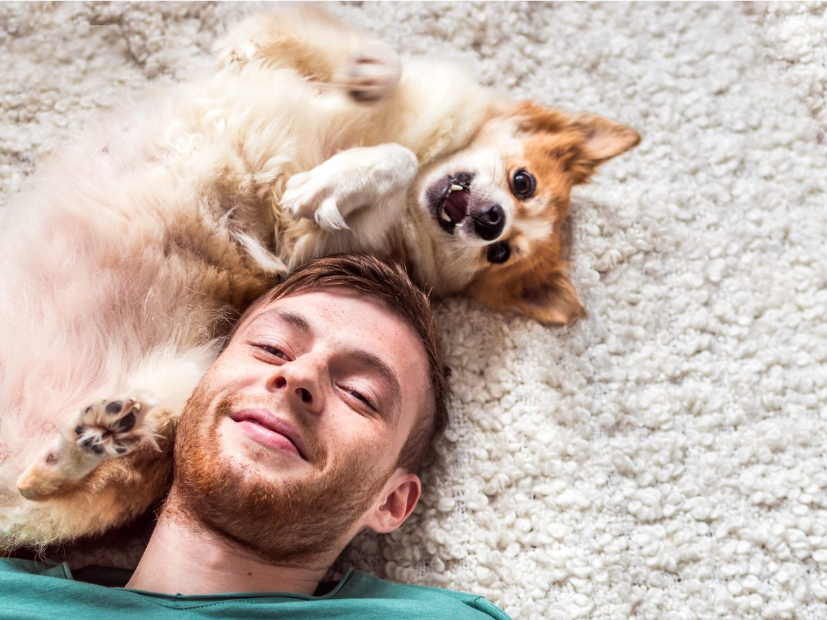 Young smiling man playing with his pet dog