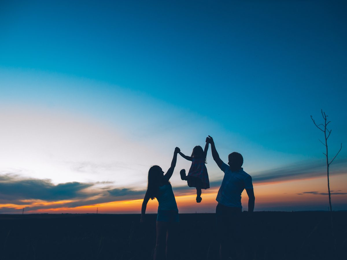 Silhouette of parents lifting up child