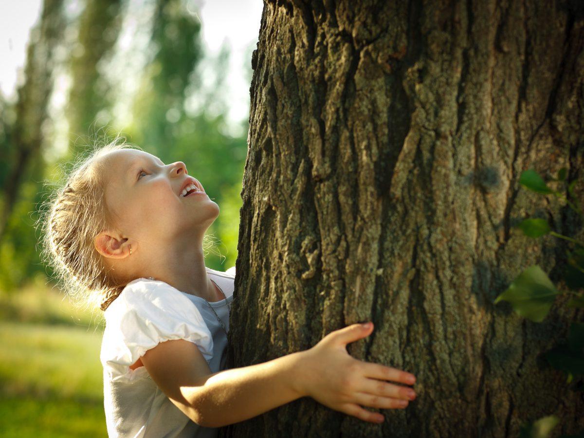 Little girl hugging tree