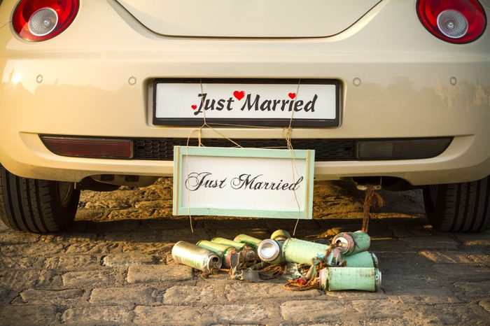 "Wedding car with a plate ""Just married"" and a bunch of a beer cans."