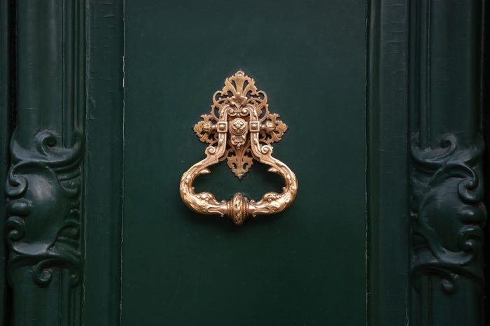 Royal style doorknocker on green door.