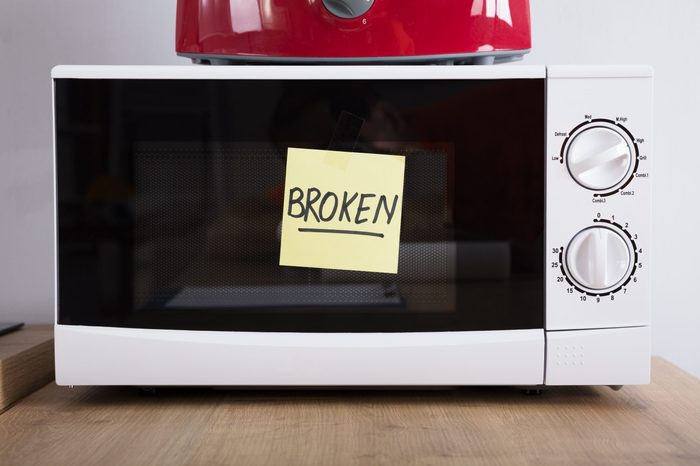Close-up Of A Microwave Oven With Adhesive Notes Showing Broken Text