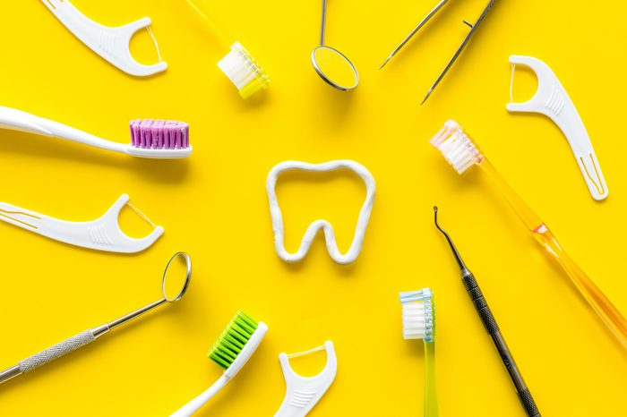 Oral hygiene concept. Tooth drawn with toothpaste near toothbrush, dental floss on yellow background top view