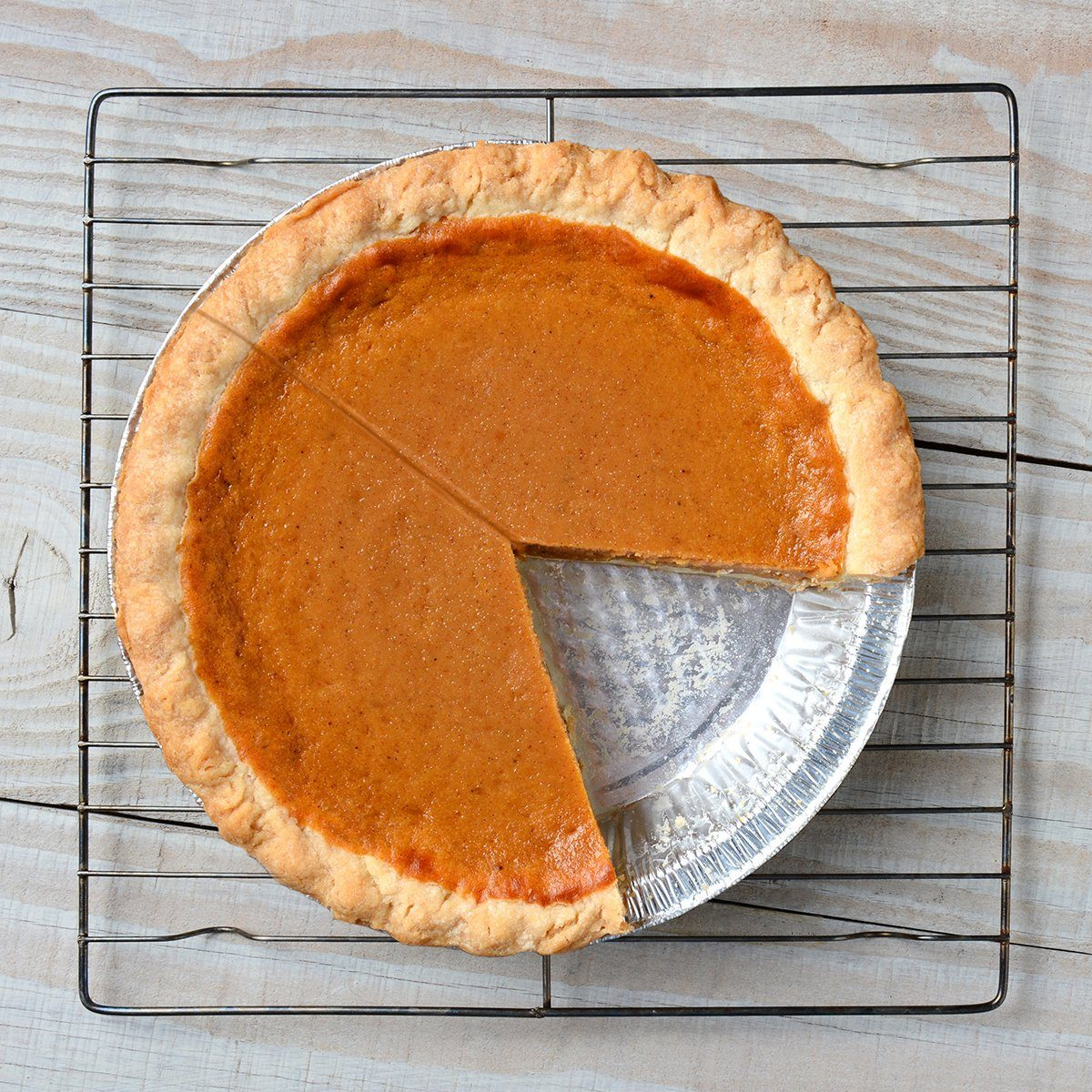 Overhead shot of a pumpkin pie with a slice cut out on a cooling rack. Horizontal format on a rustic white kitchen table.; Shutterstock ID 268798316; Job (TFH, TOH, RD, BNB, CWM, CM): TOH