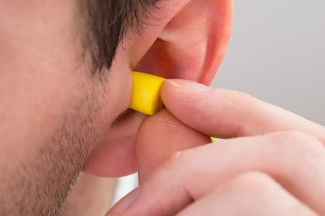 Close-up Of Person Ear With Yellow Earplug