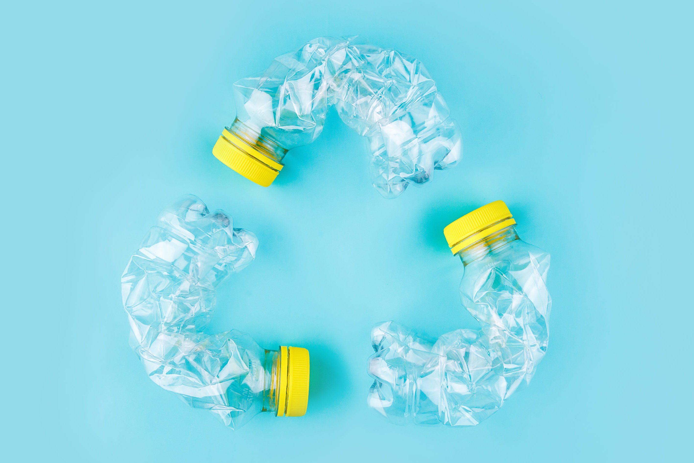 Three crashed plastic bottles on blue background form resycling sign. Plastic utilisation concept. Attractive ecological problem positive poster.