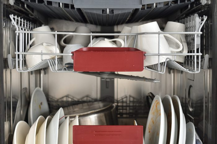 Dishwasher in the kitchen loaded with dirty dishes for washing