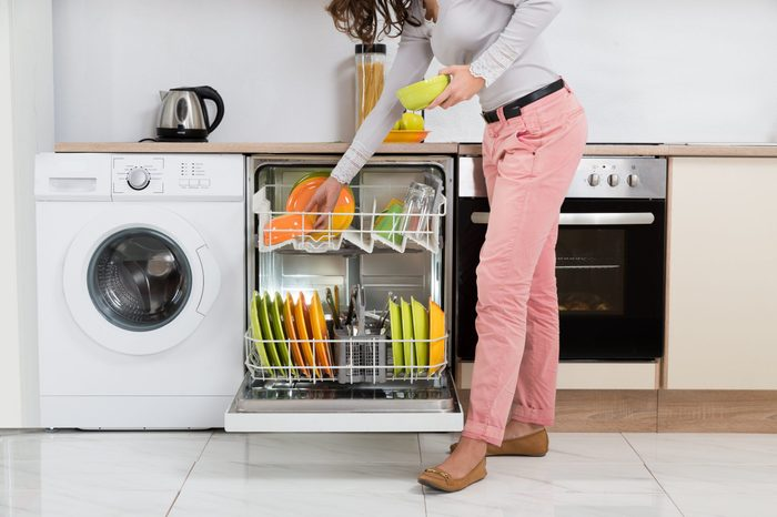Woman Standing In Kitchen Removing Bowls From Dishwasher