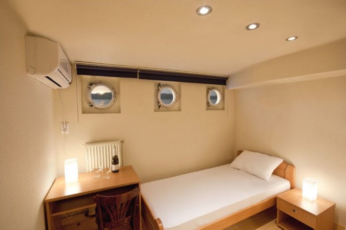 Boat deck with round windows, luxurious furnished cabin bedroom on a cruise ship, ceiling lights and wine on the desk