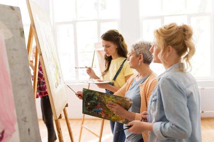 art school, creativity and people concept - women artists with easel, paint brushes and palettes painting at studio