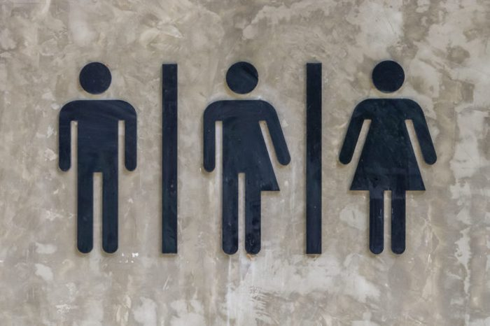 A black symbol stuck on a concrete wall to indicate that it is a toilet.