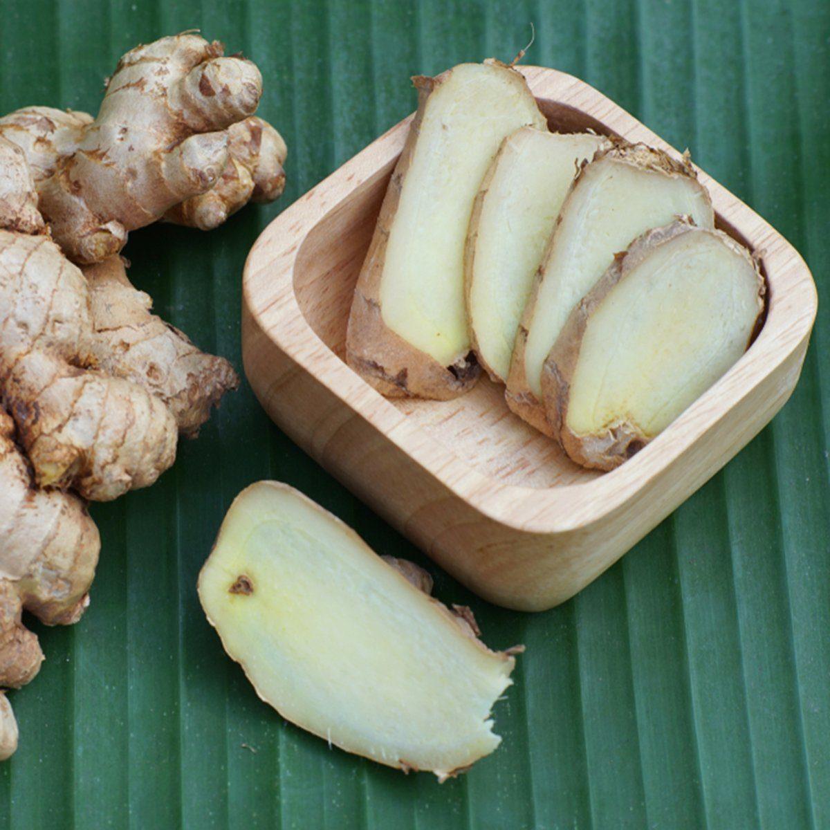 Fresh ginger root and ginger sliced on green leaf background