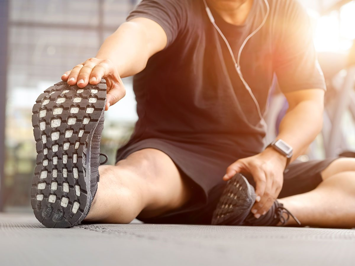 Walking 10,000 steps a day improves flexibility - man stretching at gym