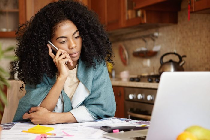 Sad African female with Afro hairstyle sitting in kitchen in front of laptop, talking on mobile phone to her husband, telling him that their family will be evicted soon because of non-payment for rent