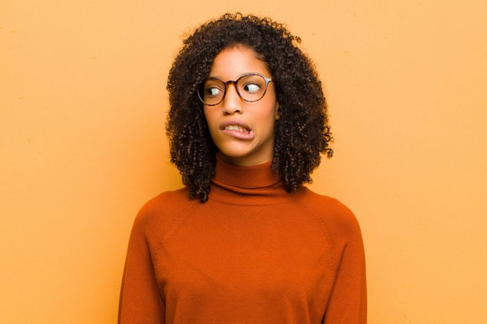 young pretty black woman feeling shocked, happy, amazed and surprised, looking to the side with open mouth against orange wall
