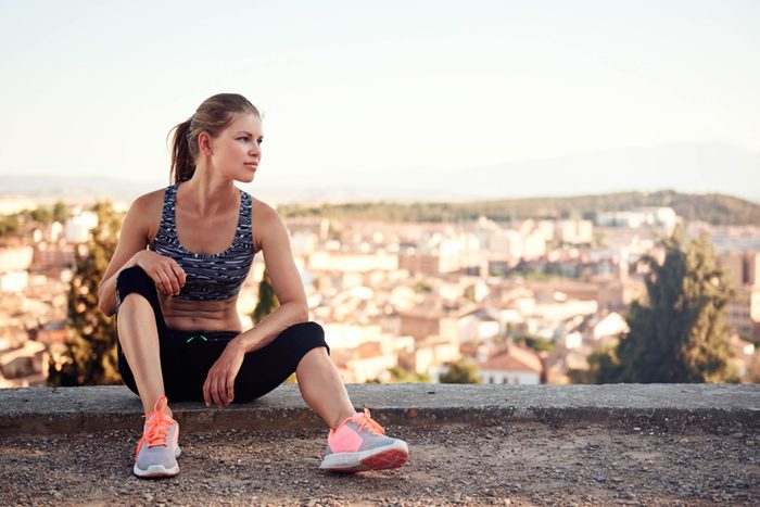 woman in workout clothes resting outdoors