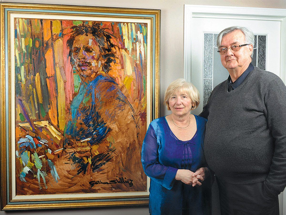 Rudy and Gloria Bies in front of a painting by Arthur Shilling