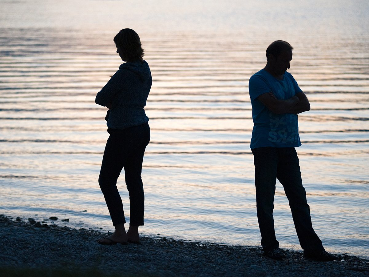 Things to Never Do After a Fight - Couple standing apart on the lake shore with arms crossed