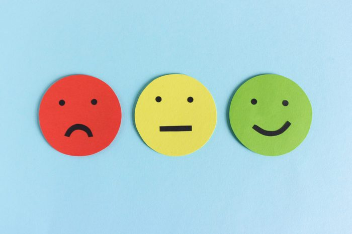 Row of three colorful smileys for expressing satisfaction, dissatisfaction and indifference composed on blue background