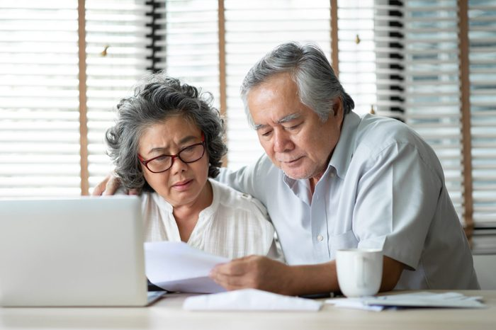 Stressed Asian Senior Couple calculate their monthly expense with laptop computer. Debts, Saving, Financials with Retirement.