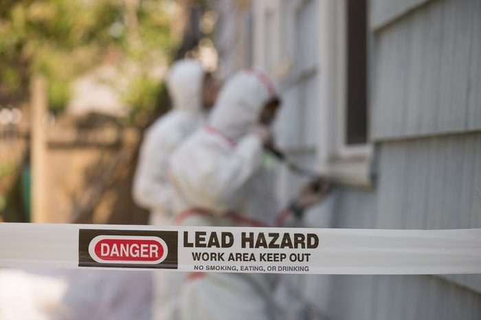 Two house painters in hazmat suits removing lead paint from an old house.