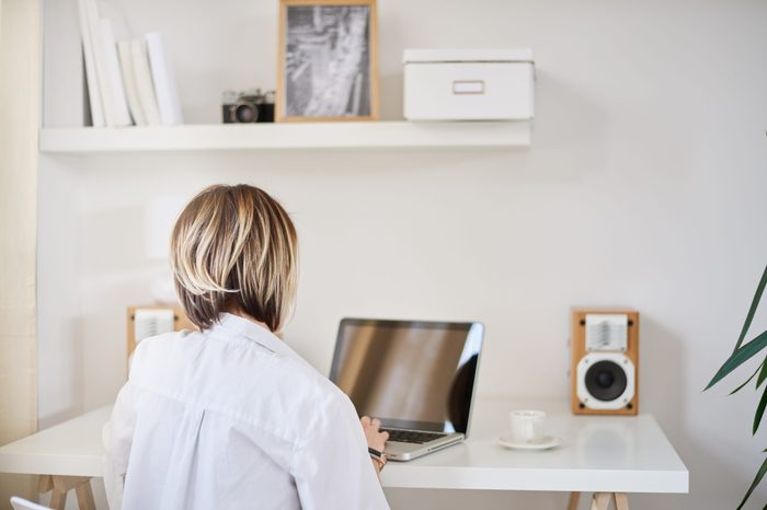 Caucasian freelancer working on laptop at home office