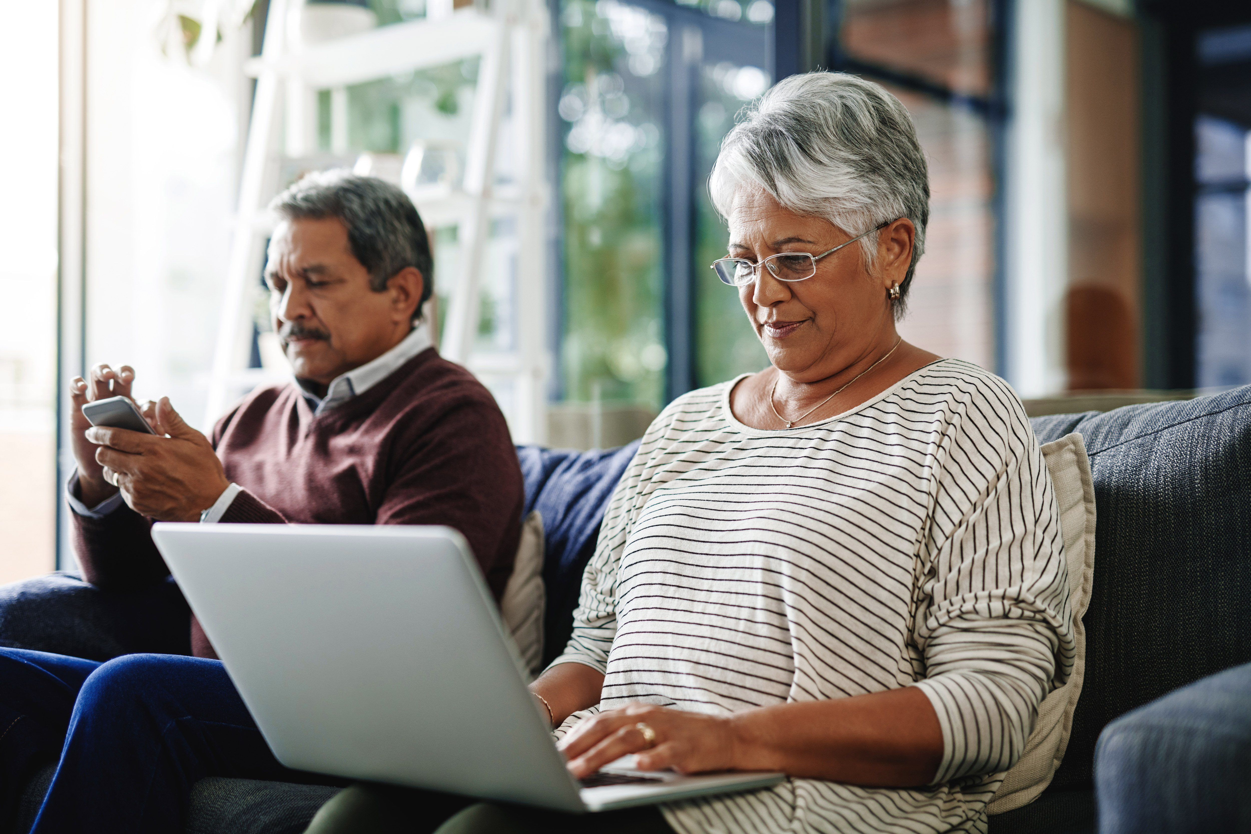 Mature woman using a laptop next to her husband using his phone. on the couch at home.