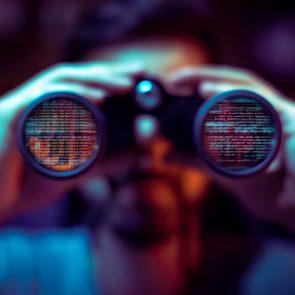 man with binoculars. the binoculars reflect computer code.