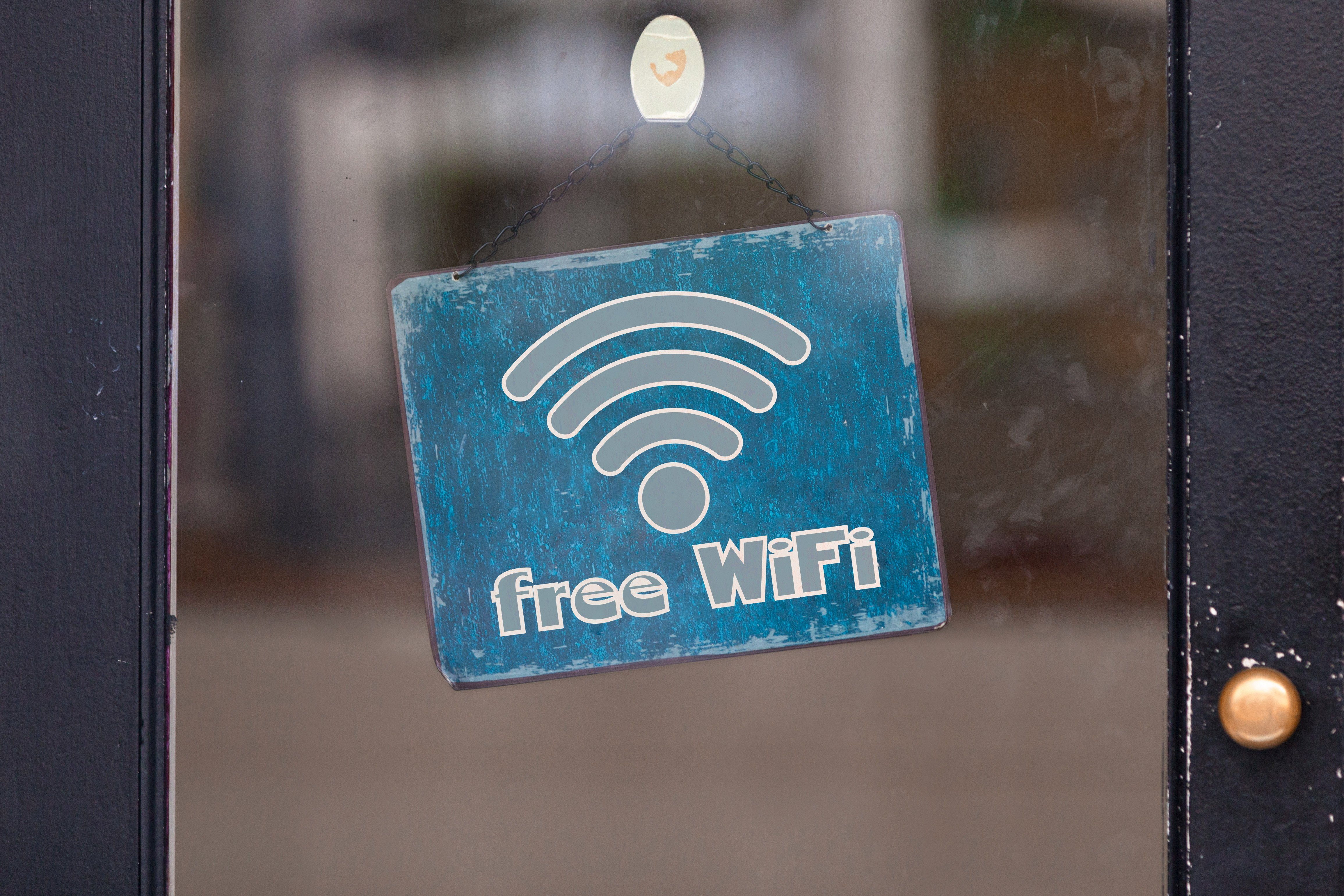 """Sign attached to a glass door saying """"Free WiFi""""."""