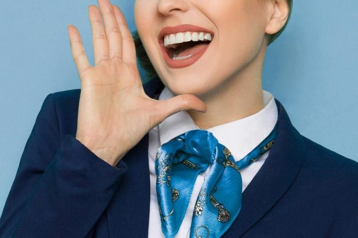 close up on woman yelling with mouth wide open and hand next to her face. flight attendant's uniform