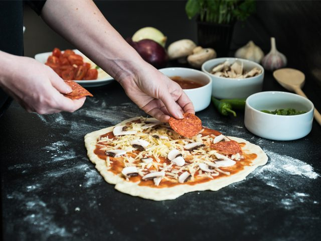 Person putting toppings on pizza