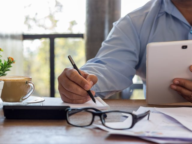 Man at desk with iPad and glasses